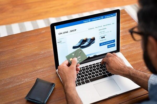 homem fazendo compra online de um calçado na promoção de ano-novo com descontos progressivos