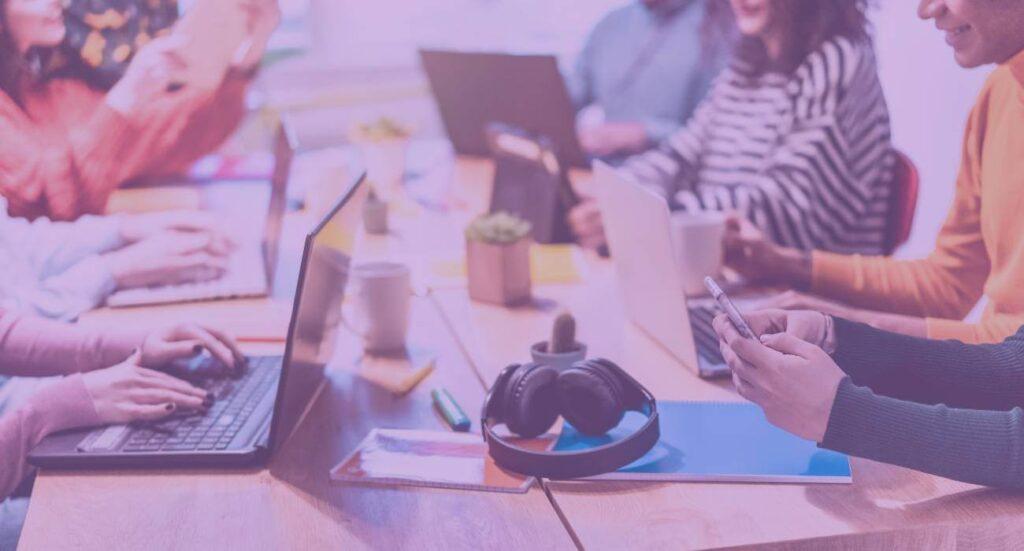 pessoas em torno de uma mesa de trabalho para criar conteúdo para e-commerce