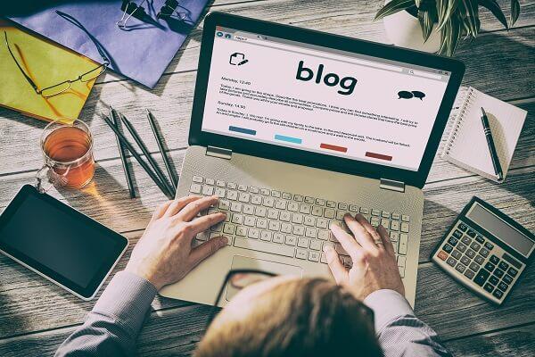 Homem trabalhando em notebook para criar conteúdo para e-commerce em um blog.